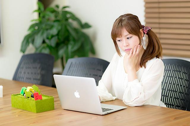 ベビーマッサージ資格発行団体を調べる女性